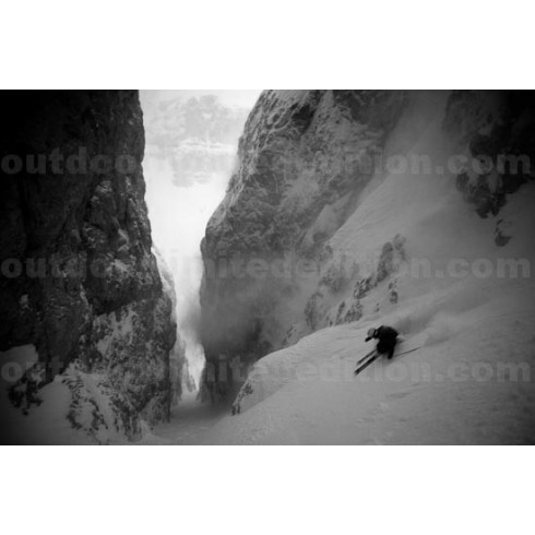 Skier going down narrow couloir