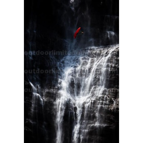 Acro paraglider in front of waterfall